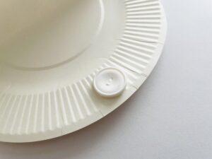 紙皿の内側にボタンを縫い留める
