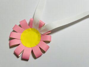 丸い画用紙に、紙テープの両端をしっかり貼ったら、貼った部分を内側にして底に貼り付ける。