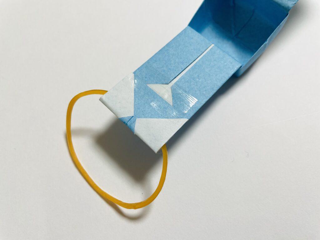 ベルト部分を折って輪ゴムをはさみ、テープで留めます